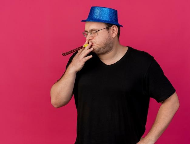 Uomo slavo adulto scontento in occhiali ottici che indossa cappello da festa blu che soffia fischio di festa