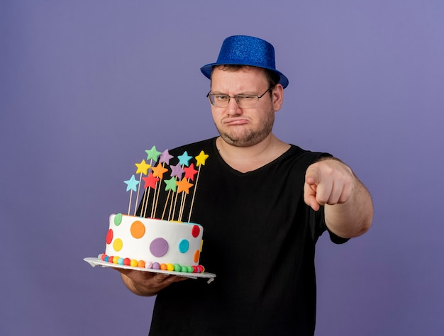Unpleased adult slavic man in optical glasses wearing blue party hat holds birthday cake pointing at camera
