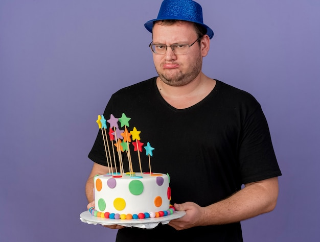 Unpleased adult slavic man in optical glasses wearing blue party hat holds birthday cake