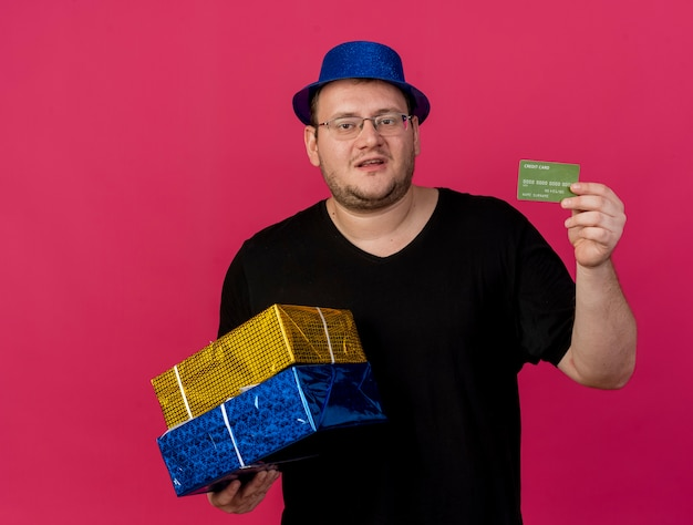 Unpleased adult slavic man in optical glasses wearing blue party hat holds gift boxes and credit card