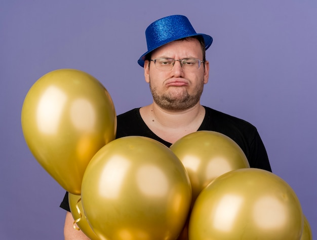 Unpleased adult slavic man in optical glasses wearing blue party hat holds helium balloons