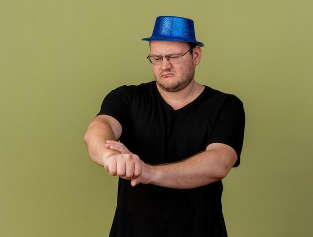 Uomo slavo adulto scontento in occhiali ottici che indossa un cappello da festa blu tiene e guarda il braccio looks