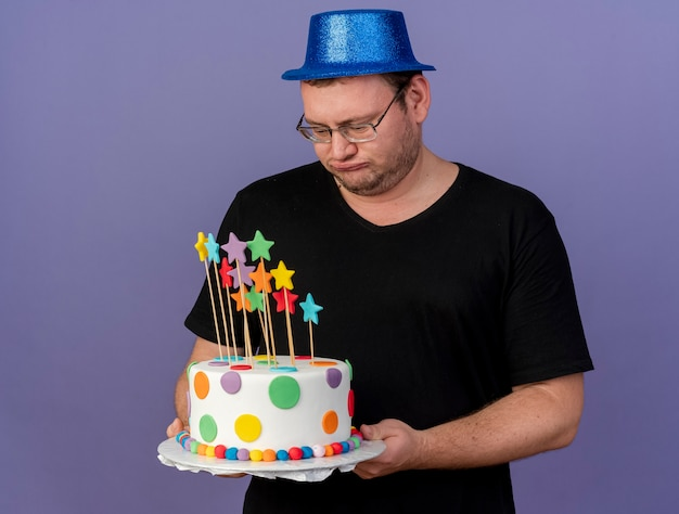 Unpleased adult slavic man in optical glasses wearing blue party hat holds and looks at birthday cake