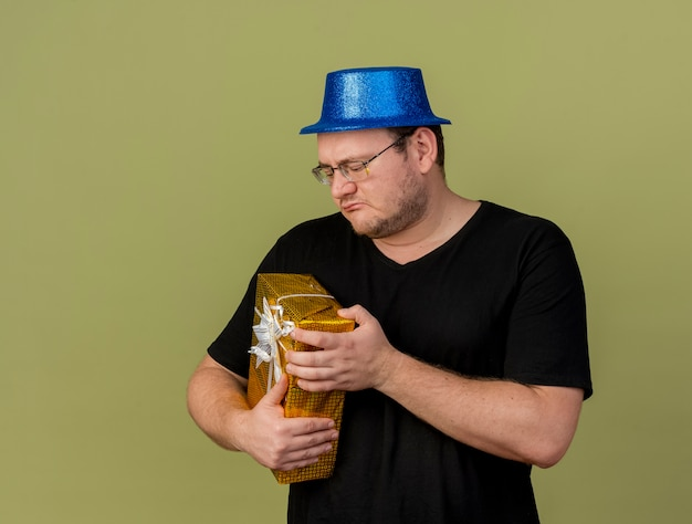 Unpleased adult slavic man in optical glasses wearing blue party hat holds and looks at gift box