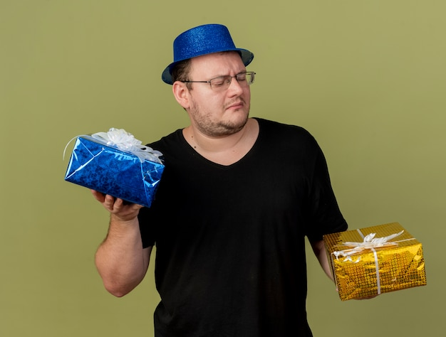 Unpleased adult slavic man in optical glasses wearing blue party hat holds and looks at gift boxes