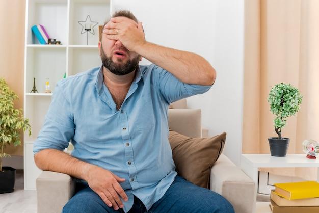 불쾌한 성인 슬라브 남자가 거실 내부의 눈을 감고 얼굴에 손을 대고 안락 의자에 앉아 있습니다.