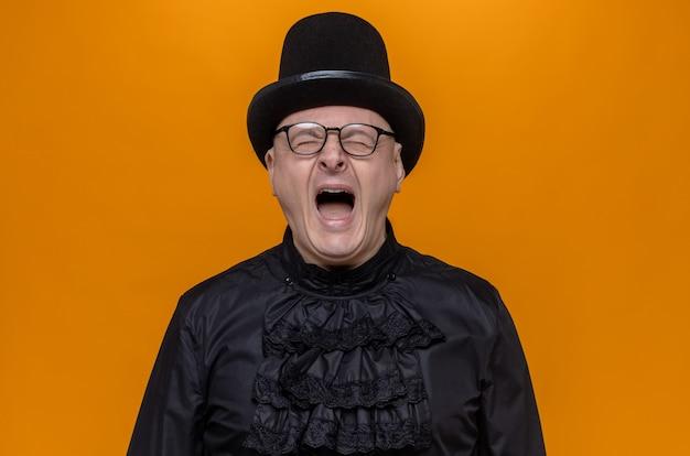 目を閉じて立って叫んでいる黒いゴシックシャツのシルクハットと光学メガネを持った不機嫌な大人のスラブ人