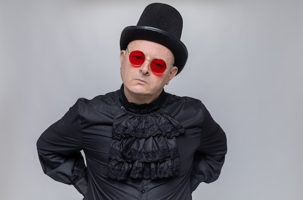 Unpleased adult slavic man with top hat and with sunglasses in black gothic shirt looking