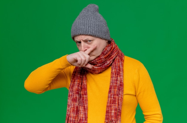 冬の帽子と首にスカーフをかぶった不機嫌な大人のスラブ人は、前を見て指で鼻を拭きます