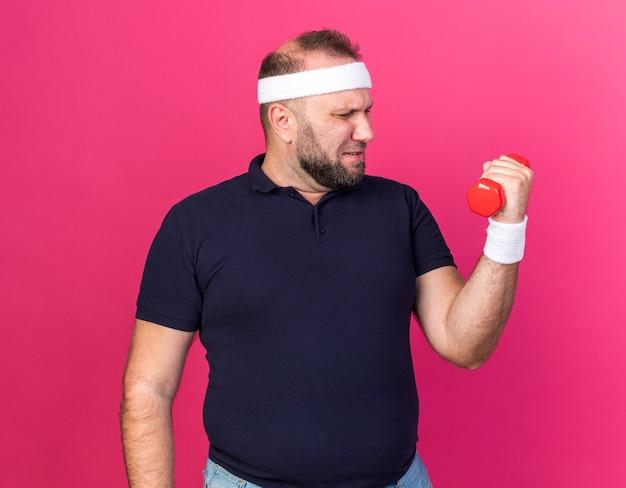 Недовольный взрослый славянский спортивный мужчина с головной повязкой и браслетами держит и смотрит на гантель, изолированную на розовой стене с копией пространства