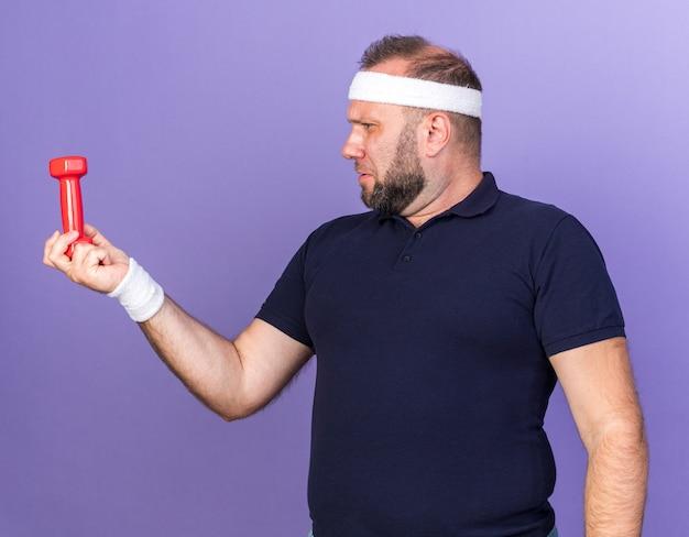 Недовольный взрослый славянский спортивный мужчина с головной повязкой и браслетами, держащий и смотрящий на гантели, изолированные на фиолетовой стене с копией пространства
