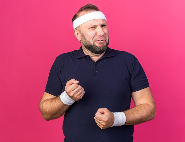 コピースペースでピンクの壁に拳を隔離しておくヘッドバンドとリストバンドを身に着けている不機嫌な大人のスラブのスポーティな男