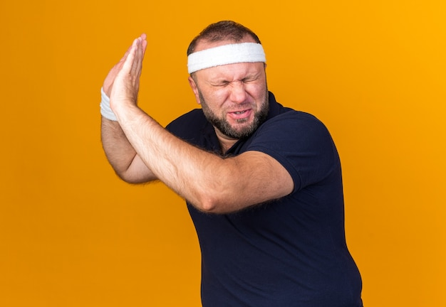 복사 공간이 오렌지 벽에 고립 된 닫힌 눈으로 서 그의 얼굴 앞에 손을 유지 머리띠와 팔찌를 착용하는 불쾌한 성인 슬라브 스포티 한 남자
