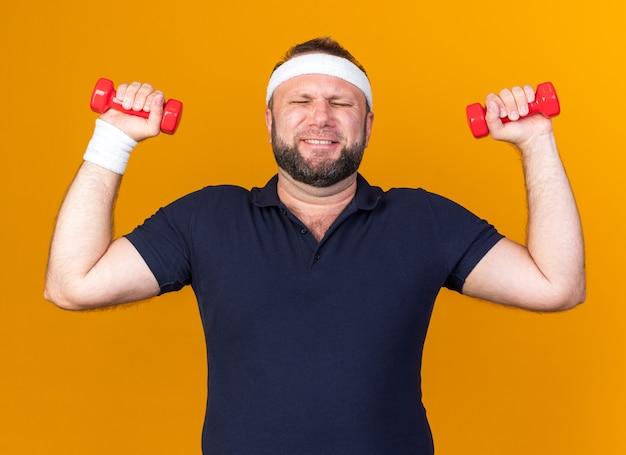 Scontento adulto slava uomo sportivo che indossa fascia e braccialetti tenendo i manubri isolati sulla parete arancione con spazio di copia