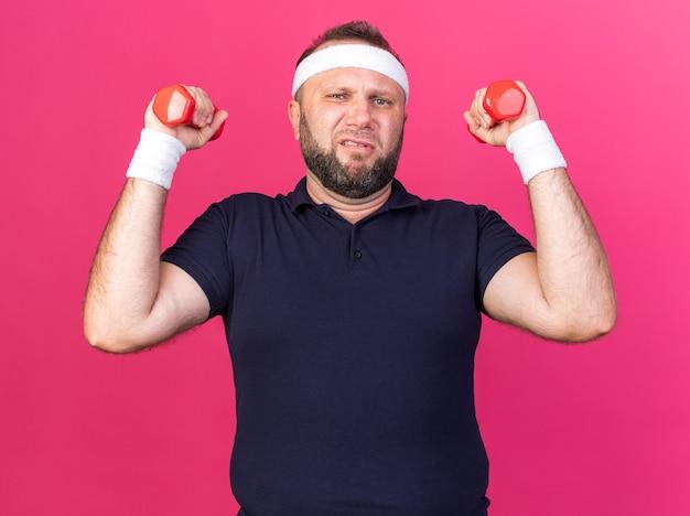 Scontento adulto slava uomo sportivo che indossa fascia e braccialetti tenendo i manubri isolati sulla parete rosa con spazio di copia