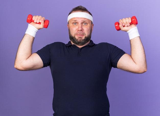 Scontento adulto slava uomo sportivo che indossa fascia e braccialetti tenendo i manubri isolati sulla parete viola con spazio di copia