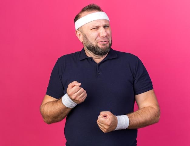 Uomo sportivo slava adulto scontento che indossa fascia e braccialetti mantenendo i pugni isolati sulla parete rosa con spazio copia