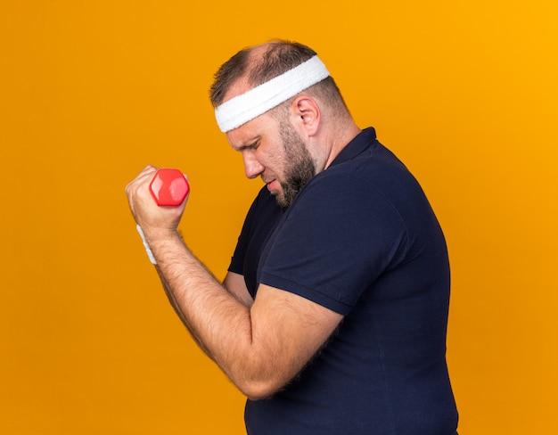 Scontento adulto slava uomo sportivo che indossa fascia e braccialetti in piedi lateralmente tenendo i manubri isolati sulla parete arancione con spazio di copia