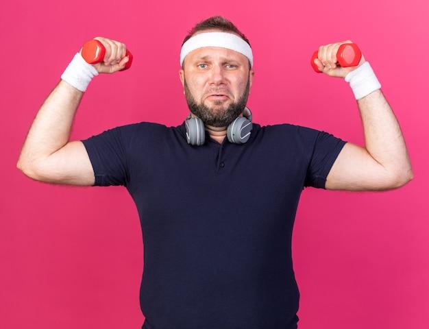 コピースペースとピンクの壁に分離されたダンベルを保持しているヘッドバンドとリストバンドを身に着けているヘッドフォンを持つ不機嫌な大人のスラブのスポーティな男