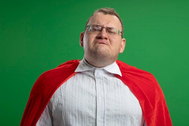 緑の壁に隔離された眼鏡をかけている赤いマントの不機嫌な大人のスラブのスーパーヒーローの男
