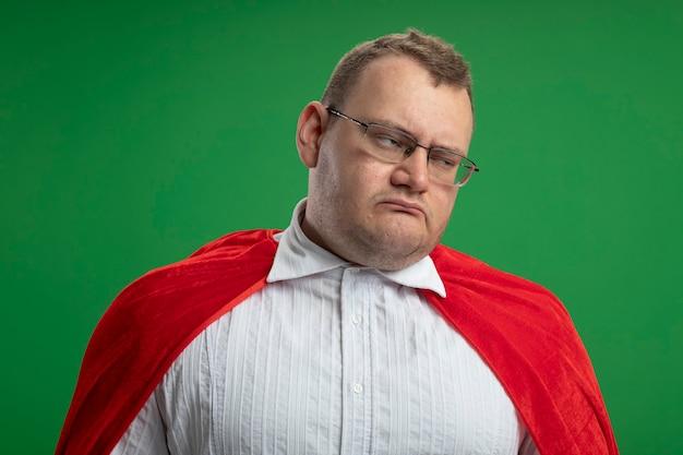緑の壁に隔離された側を見て眼鏡をかけている赤いマントの不機嫌な大人のスラブのスーパーヒーローの男