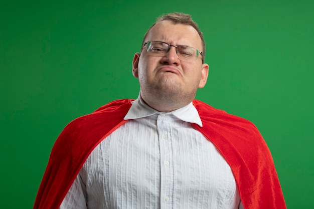 Uomo adulto dispiaciuto del supereroe slavo in mantello rosso con gli occhiali isolati sulla parete verde