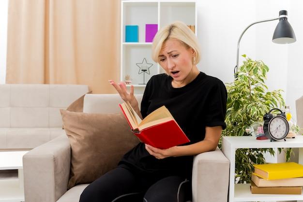 Soddisfatta bella donna russa bionda si siede sulla poltrona che tiene e guardando il libro alzando la mano all'interno del soggiorno