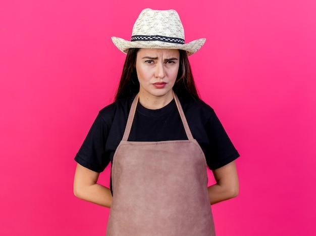 Недовольная красивая девушка-садовник в униформе в садовой шляпе, держась за руки за спиной, изолированной на розовом