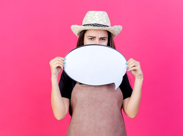 Soddisfatta bella ragazza giardiniere in uniforme che indossa il cappello da giardinaggio coprì il viso con il fumetto isolato su sfondo rosa