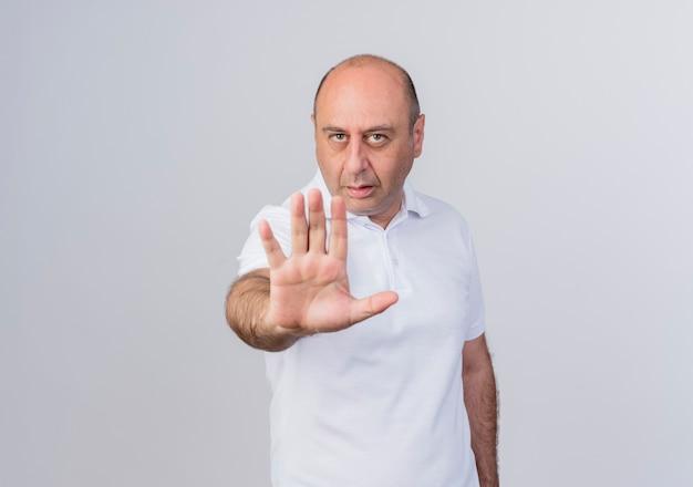 Недовольный случайный зрелый бизнесмен делает стоп-жест на камеру, изолированную на белом фоне с копией пространства