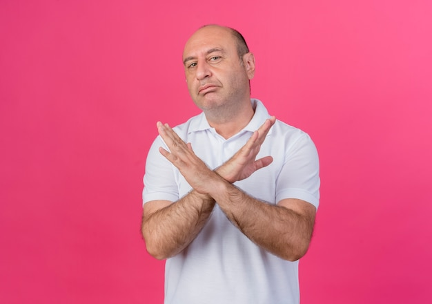 Unpleased casual mature businessman keeping hands crossed doing no gesture isolated on pink background with copy space