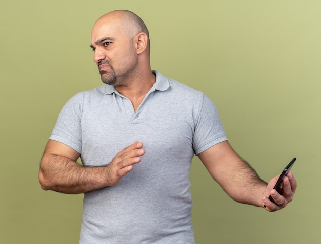 Unpleased casual middle-aged man holding mobile phone doing refusal gesture looking at side isolated on olive green wall