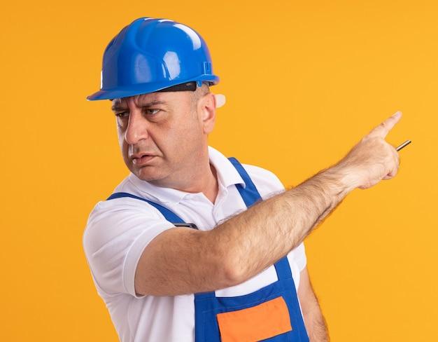 制服を着た不機嫌な白人の大人のビルダーの男は、鉛筆を保持し、オレンジ色の側を指しています