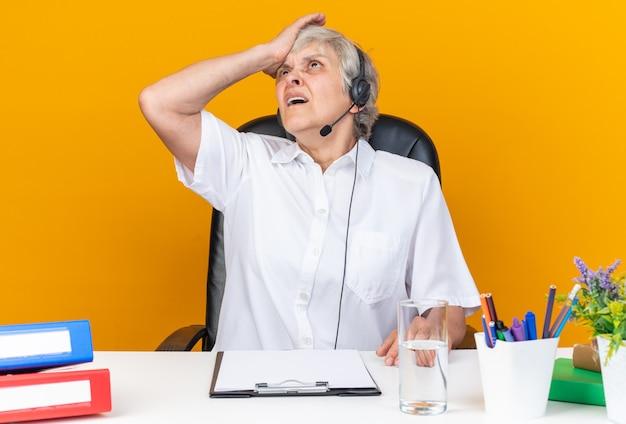 Operatore di call center femminile caucasico scontento sulle cuffie seduto alla scrivania con strumenti da ufficio che mette la mano sulla fronte guardando in alto