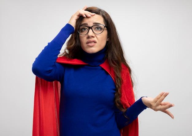 Недовольная кавказская девушка-супергерой в красной накидке в оптических очках кладет руку на лоб на белом