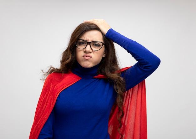Недовольная кавказская девушка-супергерой в красной накидке в оптических очках кладет руку на голову на белом