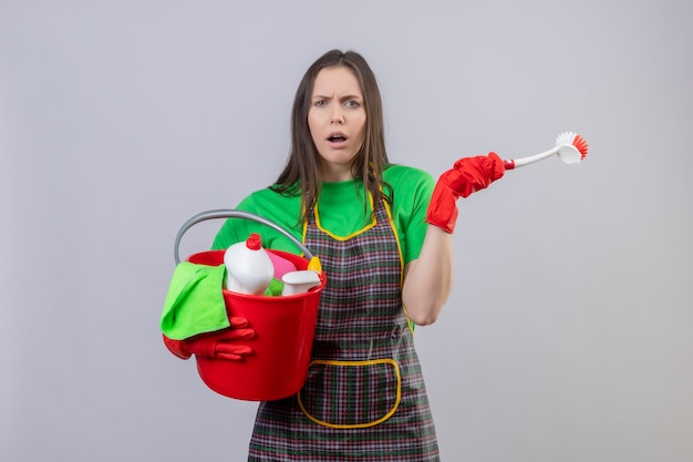 Unpleased cleaning young woman wearing uniform in red gloves holding cleaning tools on isolated white wall