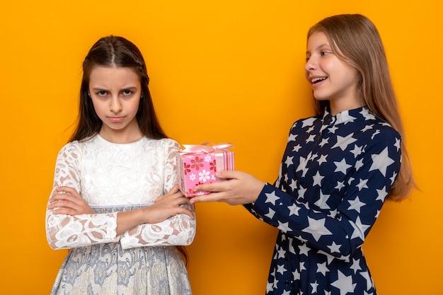Unpleased crossing hands two little girls on birthday present