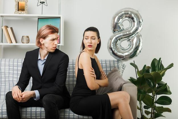 幸せな女性の日に若いカップルがリビングルームで背中合わせにソファに座ってお互いを見ている不愉快な交差点