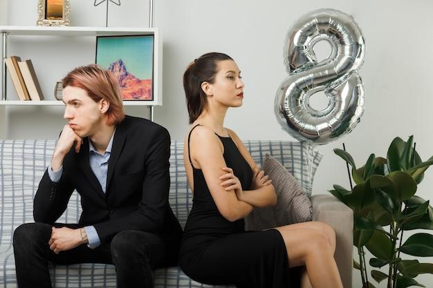 不愉快な交差点は、リビングルームで背中合わせにソファに座って幸せな女性の日に若いカップルを手渡します
