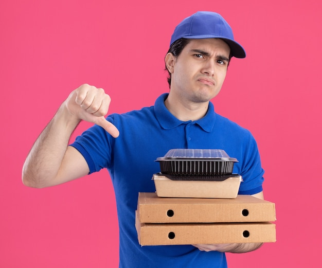 Unpleased delivery man in blue uniform and cap holding pizza packages with food container and paper food package on them looking at front showing thumb down