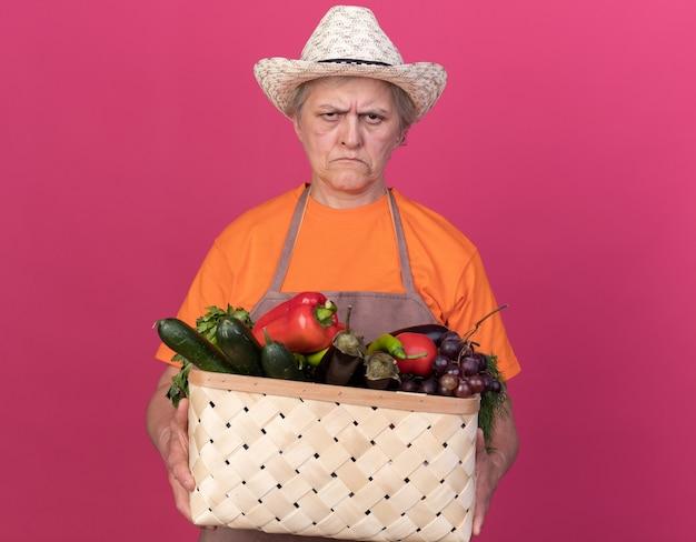 野菜のバスケットを保持しているガーデニング帽子をかぶっている不機嫌な年配の女性の庭師