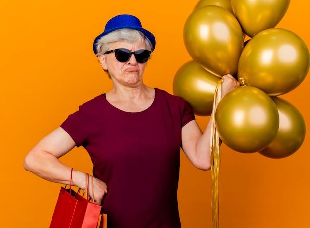 파티 모자를 쓰고 태양 안경에 불쾌한 노인 여성이 헬륨 풍선과 종이 쇼핑백을 보유하고 있습니다.