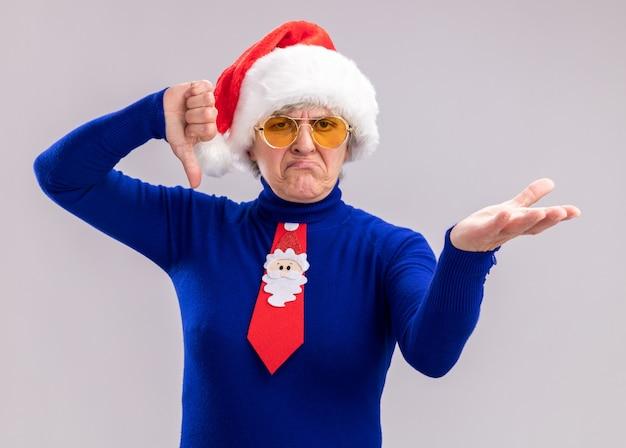 サンタの帽子とサンタのネクタイの親指を下に置き、コピースペースのある白い壁に隔離された手を開いたままにしておくサングラスの不機嫌な年配の女性