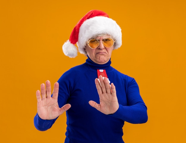 Unpleased elderly woman in sun glasses with santa hat and santa tie holds hands open gesturing no sign isolated on orange wall with copy space
