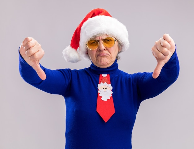 Unpleased elderly woman in sun glasses with santa hat and santa tie thumbing down isolated on white wall with copy space