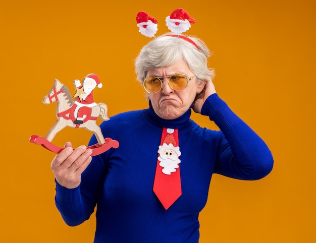 Unpleased elderly woman in sun glasses with santa headband and santa tie holding and looking at santa on rocking horse decoration isolated on orange background with copy space