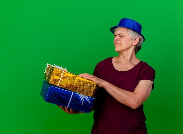 Donna anziana dispiaciuta che indossa il cappello del partito che tiene ed esamina i contenitori di regalo sul verde