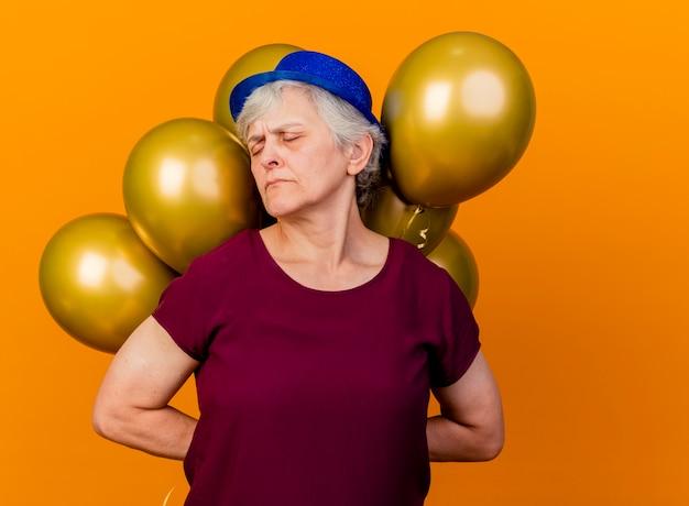 파티 모자를 쓰고 불쾌한 노인 여성이 오렌지에 닫힌 눈으로 헬륨 풍선을 들고 있습니다.