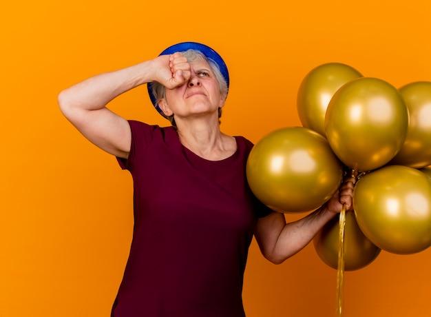 La donna anziana dispiaciuta che porta il cappello del partito tiene i palloni dell'elio e mette il pugno sull'occhio che osserva in su isolato sulla parete arancione con lo spazio della copia